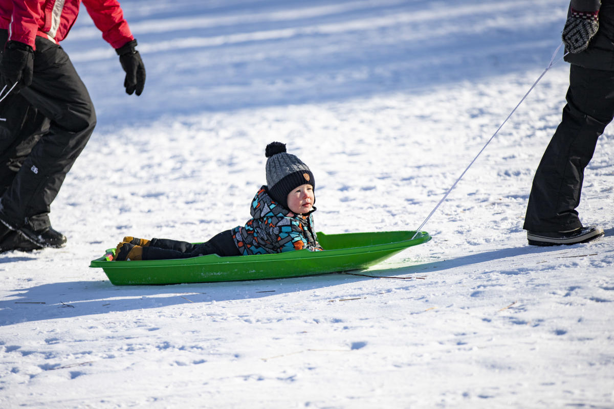 Little boy getting pulled on a sled at Pinehurst Park