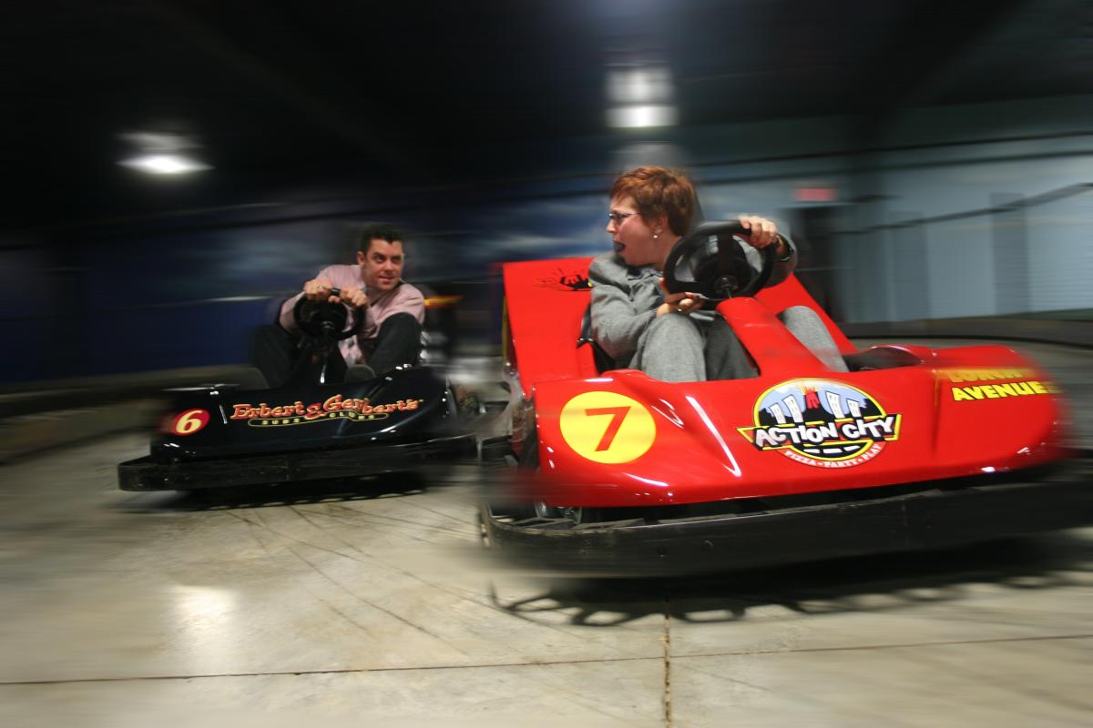 Two adults racing in go-karts at Action City