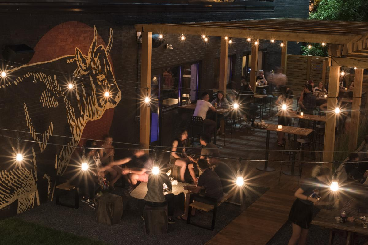 People dining outside on the patio at the Lakely at night