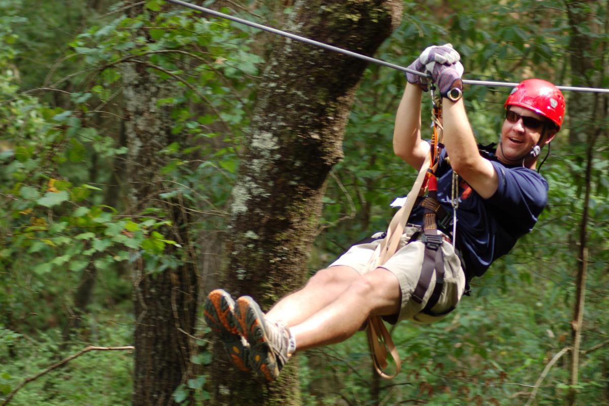 Man ziplining among trees in Fayetteville North Carolina