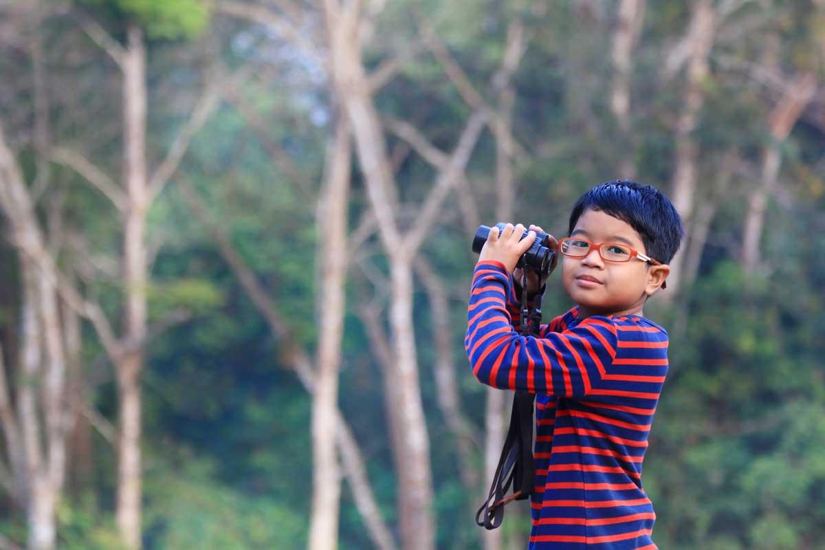 little boy taking a break from bird watching