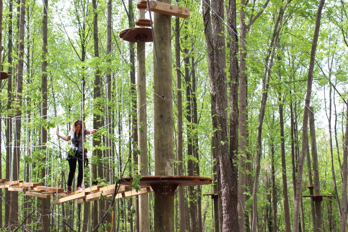 Woman crossing an elevated bridge at TreeTrekkers