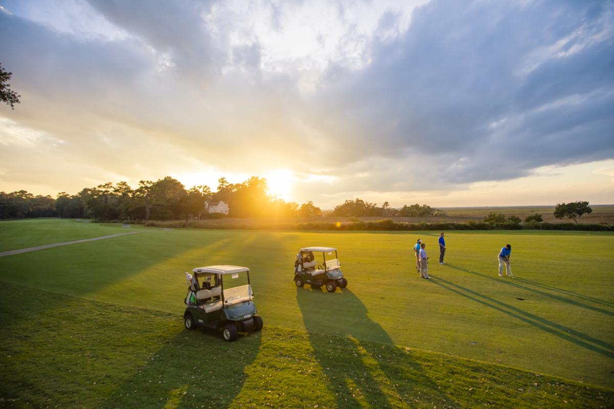 A group tees off under the light of a golden sunset at a golf course in Georgia's Golden Isles.