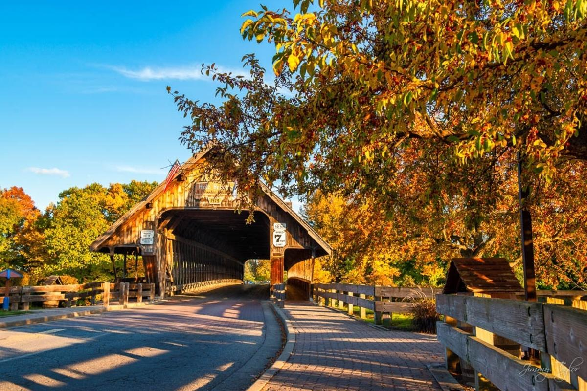 Shadows of the fall trees casting over the cobblestone in front of the Holz-Brucke Covered Bridge in Frankenmuth