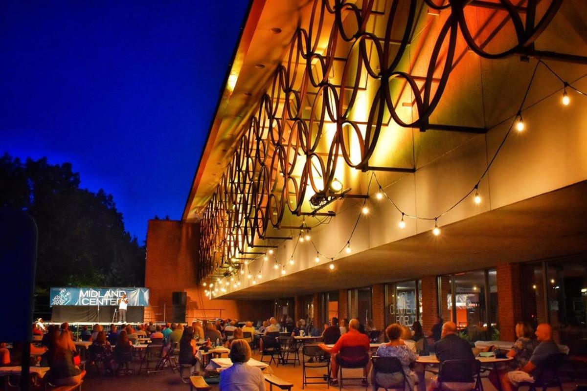 Outdoor seating for Curbside Comedy at Midland Center for the Arts, with the architecture of the building beautifully lit