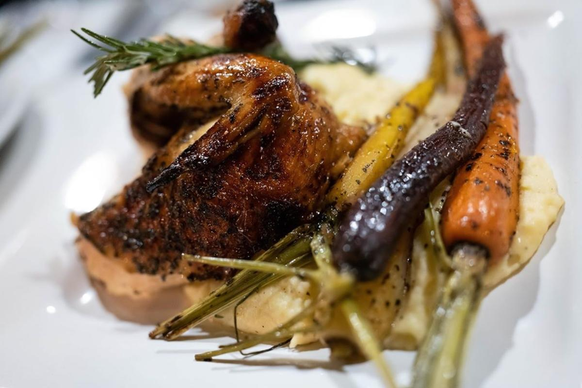 Roasted chicken and tri-colored carrots, perfectly plated at Artisan Urban Bistro in Old Town Saginaw