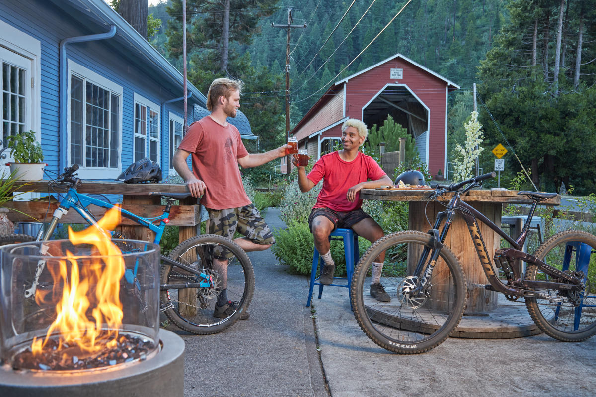 Two mountain bikers with their bikes nearby sit and cheers with their beers on a patio at Westfir Lodge in the evening. There is a fire in a firepit in the foreground and the red Office Covered Bridge in the background