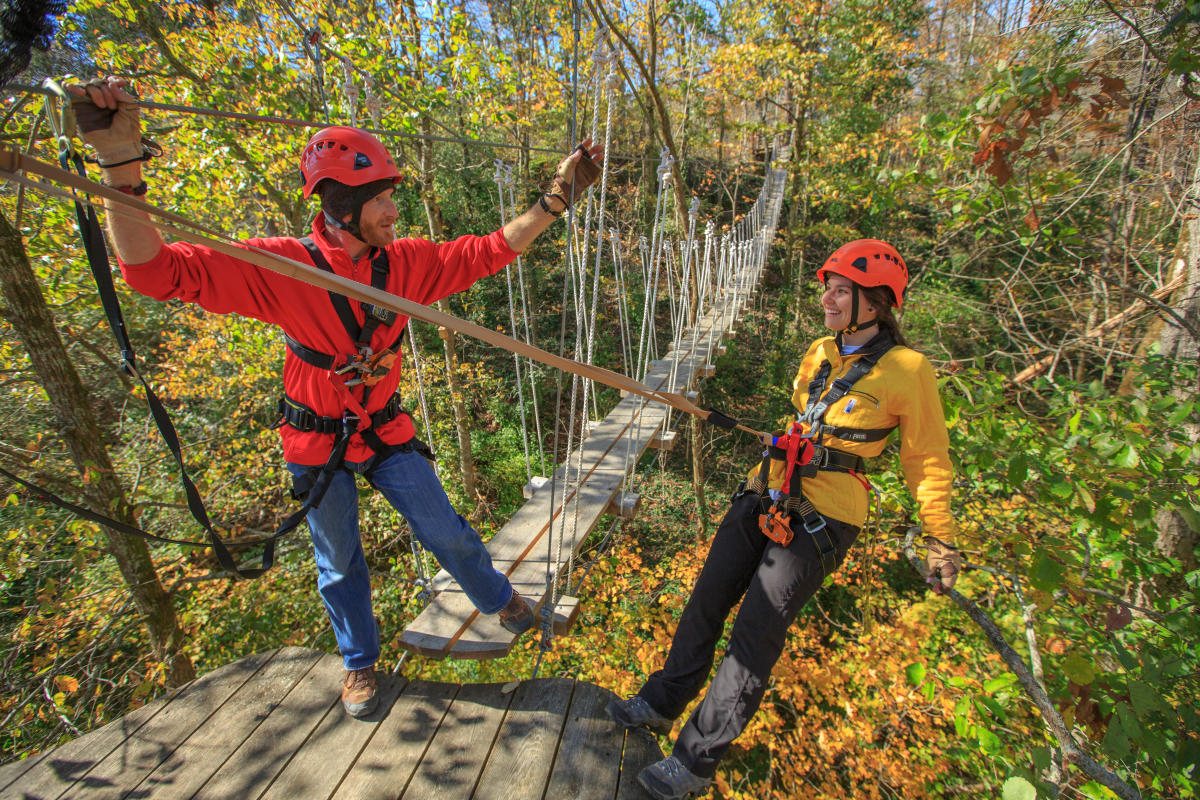 Two people on zipline at Boone Creek Outdoors in the fall.