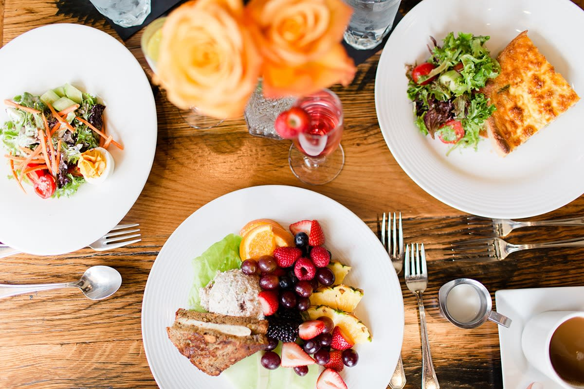 Top down view of three plates of freshly made salad, fruit, and sandwiches on a wooden table.