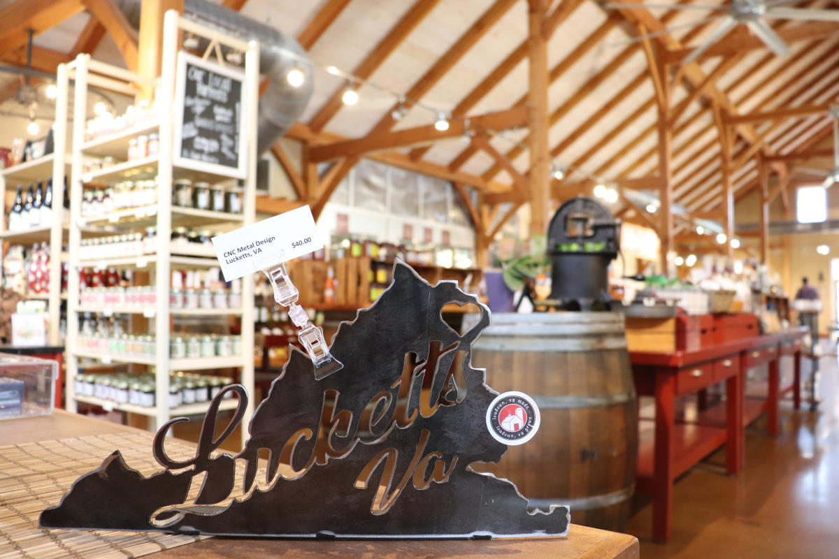 """A metal sign carved in the shape of Virginia with """"Lucketts VA"""" carved out of the middle sits on a table in front of rows of local products at Roots 657 Cafe & Local Market"""