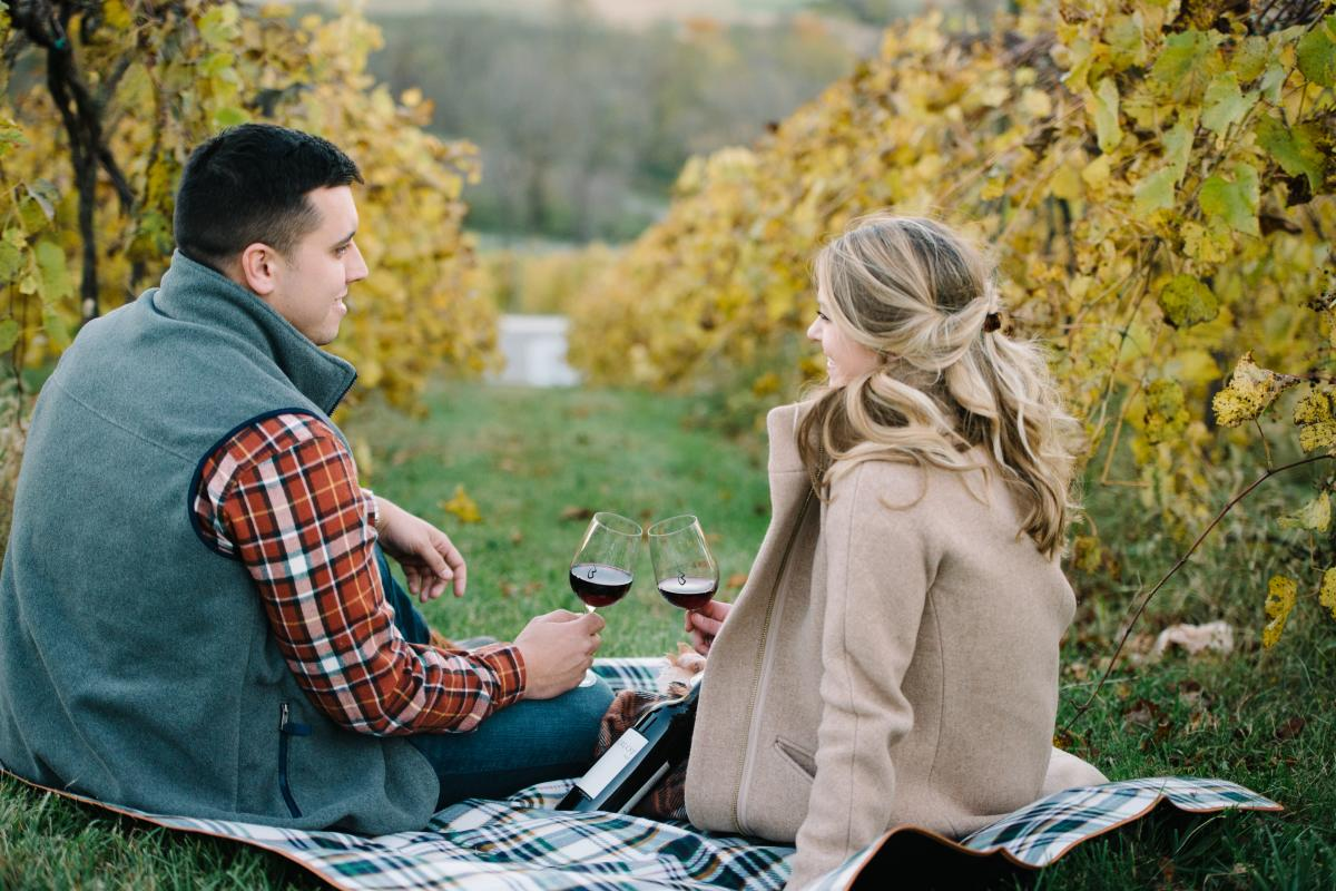 Couple drinking wine while sitting on the ground between in the vines of Bluemont Vineyard