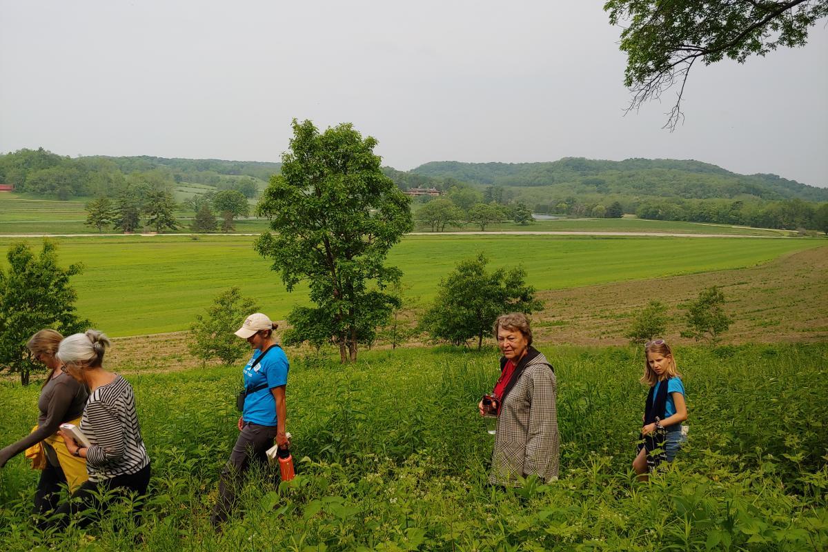 Women walk along a trail with lush green fields in the backdrop
