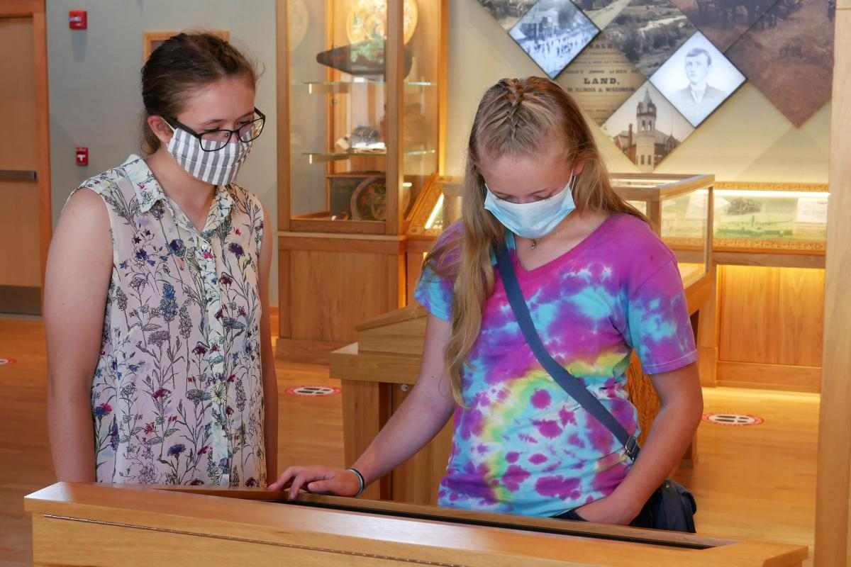 Two teenage girls wearing masks read an exhibit at the Norwegian Heritage Center