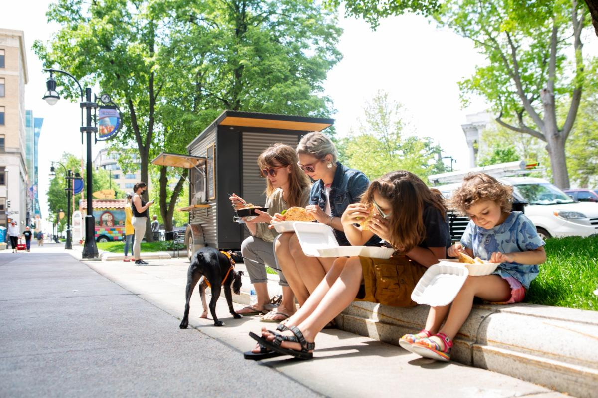 A family enjoys food from a food cart while sitting on a curb in downtown Madison