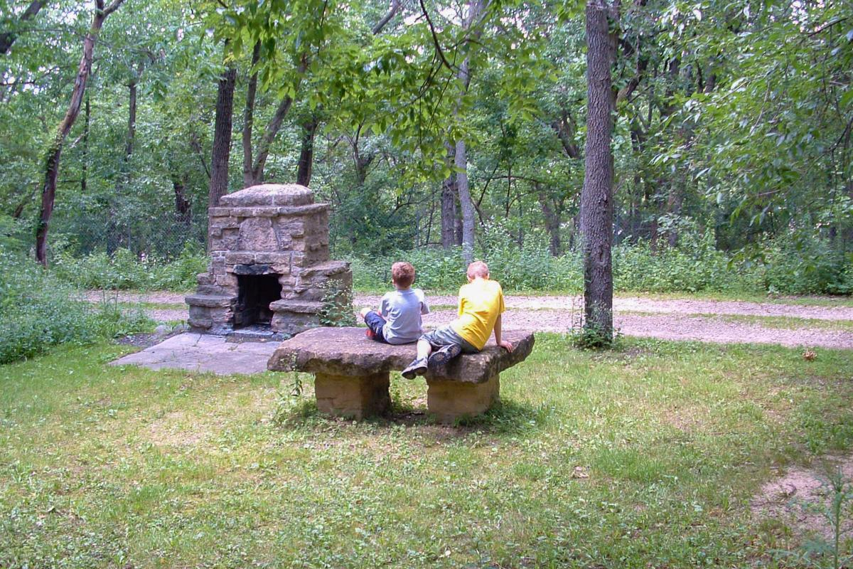 Two children sit on a bench in front of a brick fire pit at Hoyt Park
