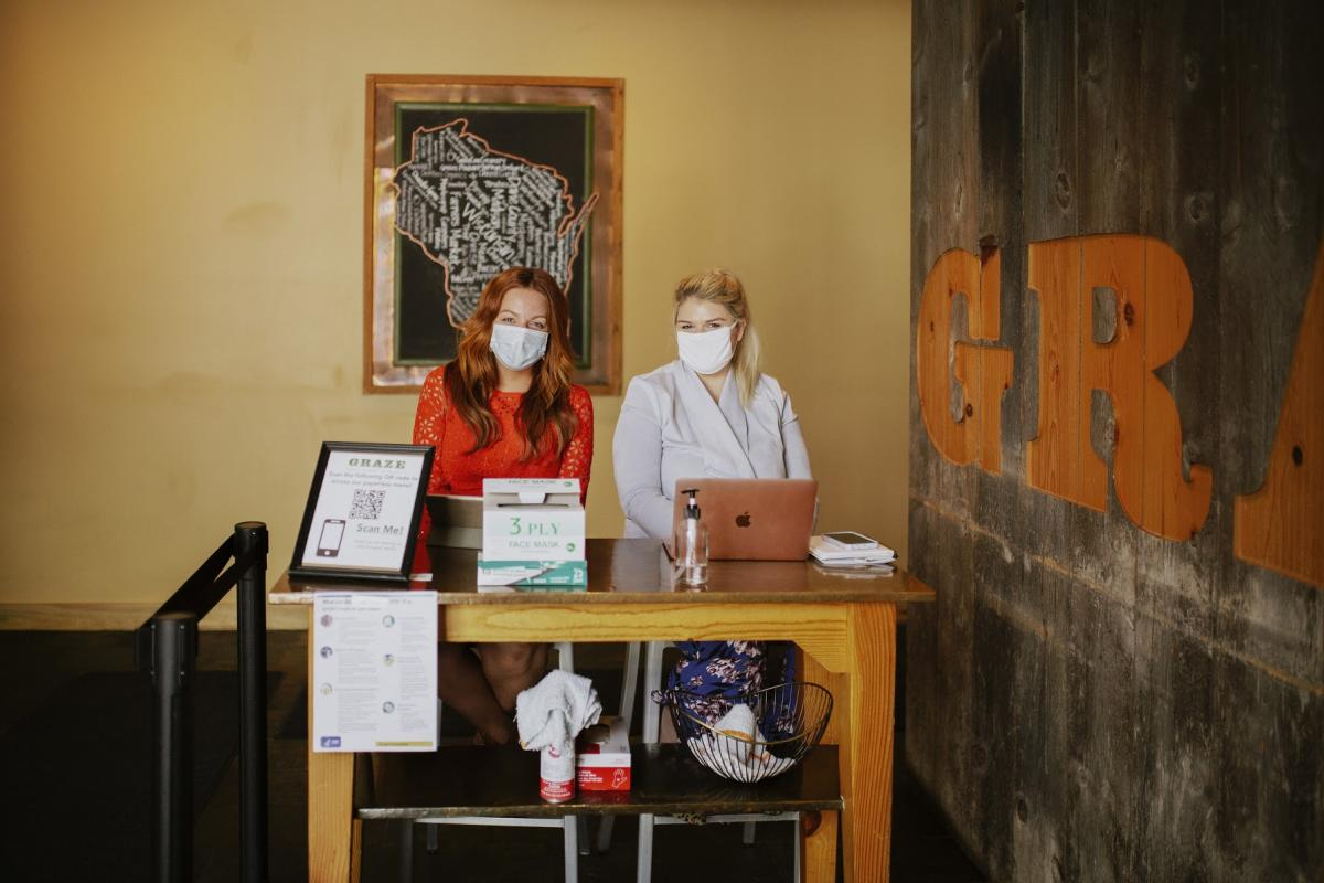 Two women wearing masks sit at the front desk at Graze