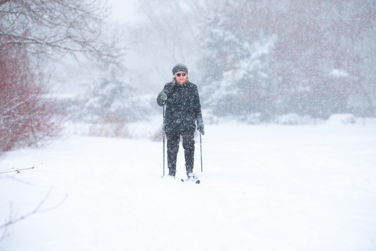 A woman cross-country skiing as snow falls