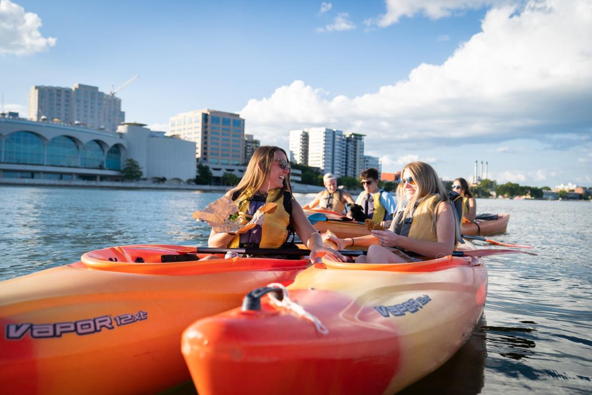 A group of friends enjoy sandwiches while kayaking in front of Monona Terrace on Lake Monona