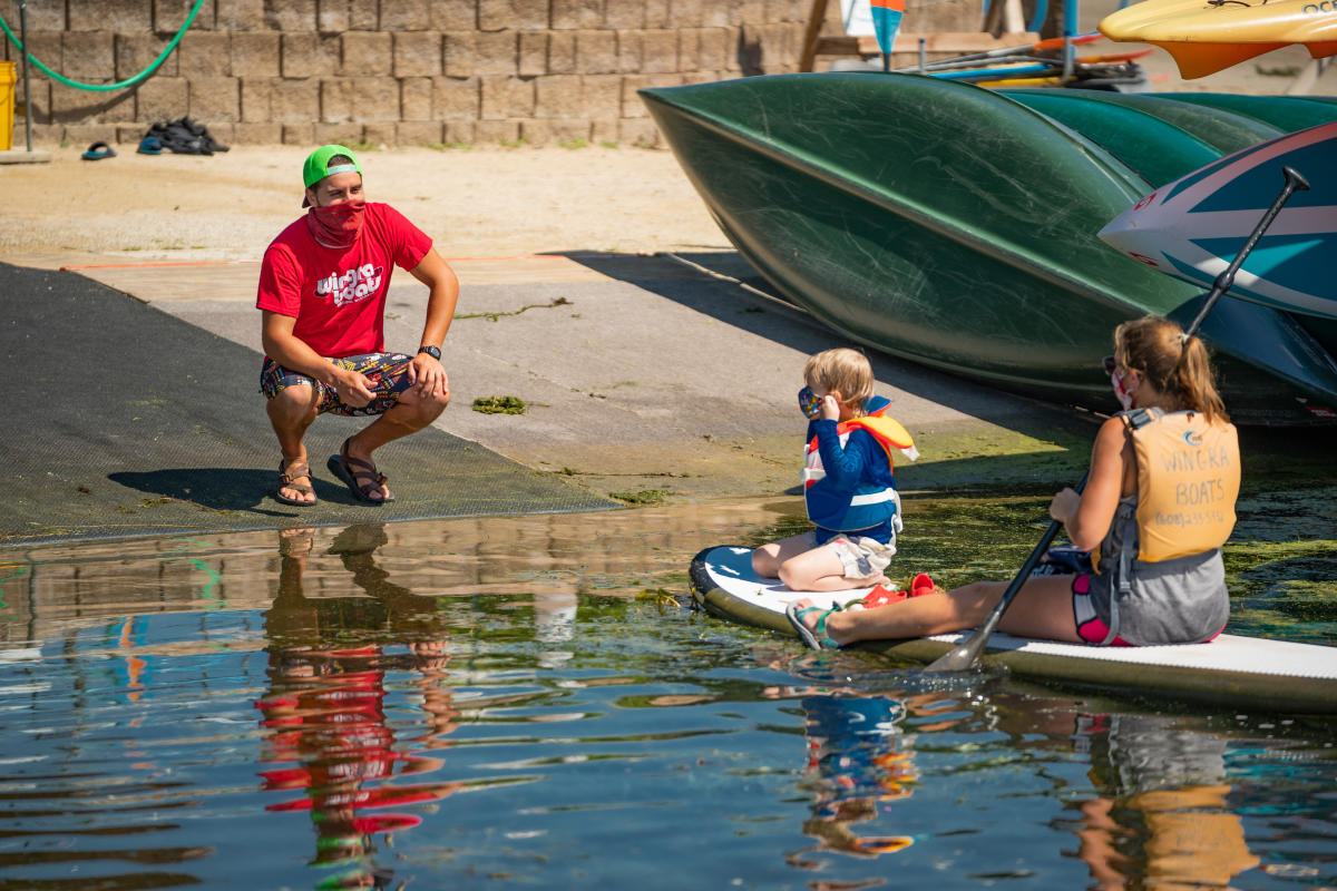 A masked Madison Boats employee awaits a woman and child to return their paddleboard