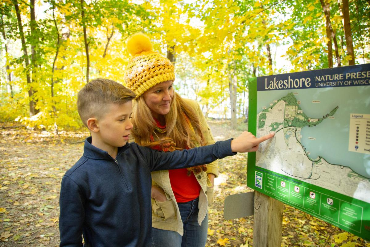 A mother and son view the Lakeshore Nature Preserve trail map