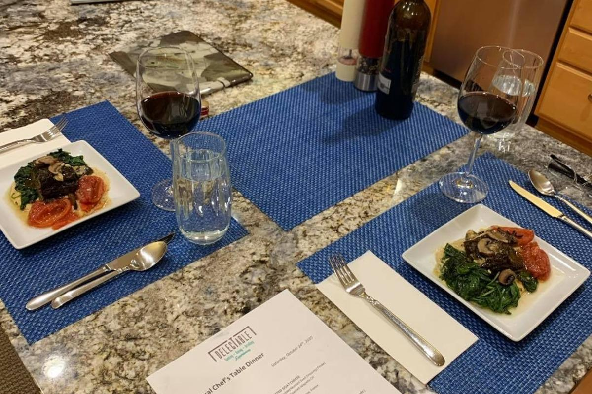A table setting with dinners for two and a virtual presentation on a laptop next to them