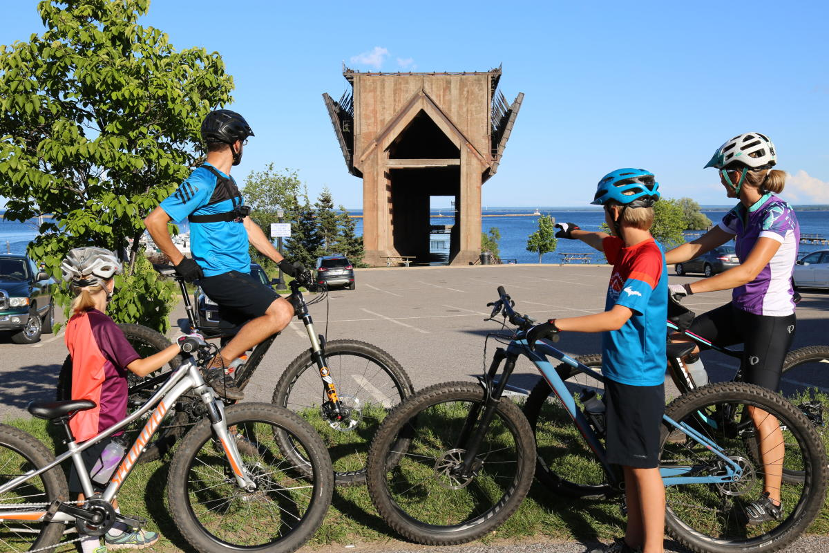 A family takes a break from cycling to enjoy the sites along the 17-mile Multi-use path.