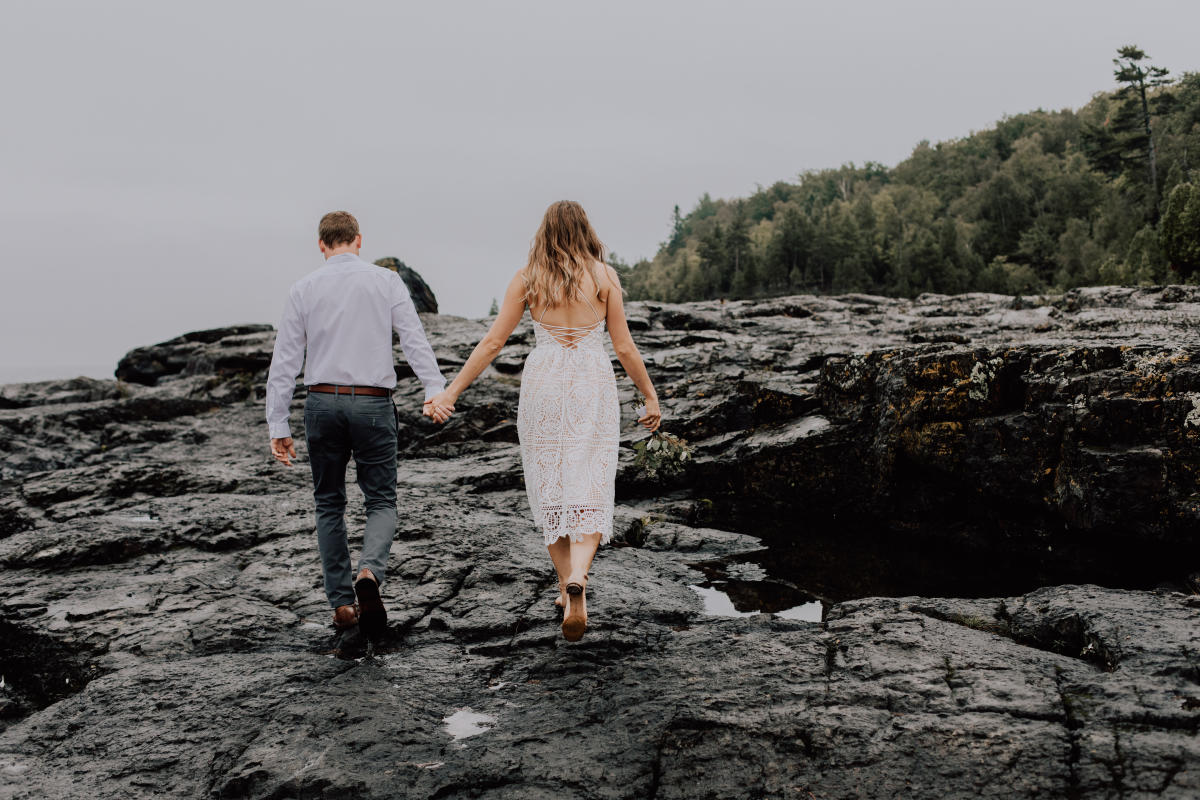 A newlywed couple holds hands on the Black Rocks in Marquette