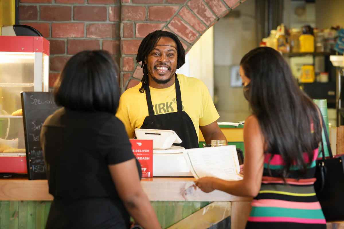 Customers interact with cashier at Kirk's Jerk Chicken.