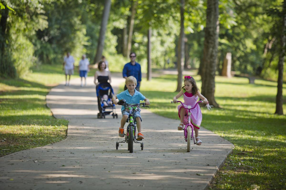 Two Children Biking Down The Oconee River Greenway In Milledgeville, GA