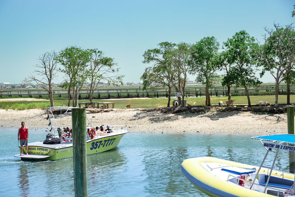 Boat pulling up to Goat Island in Murrells Inlet