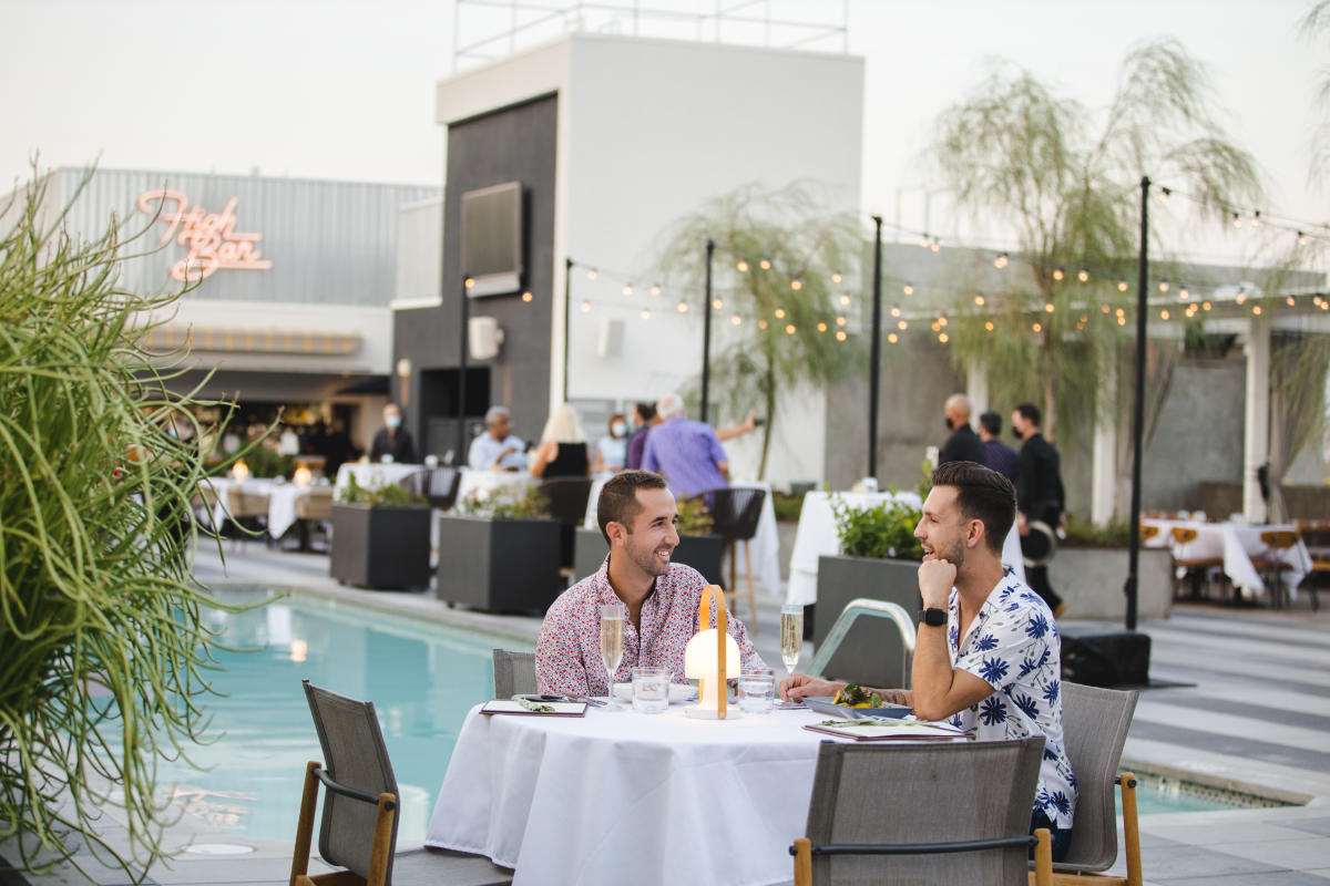 Couple dines on rooftop of the Kimpton Rowan next to the pool.