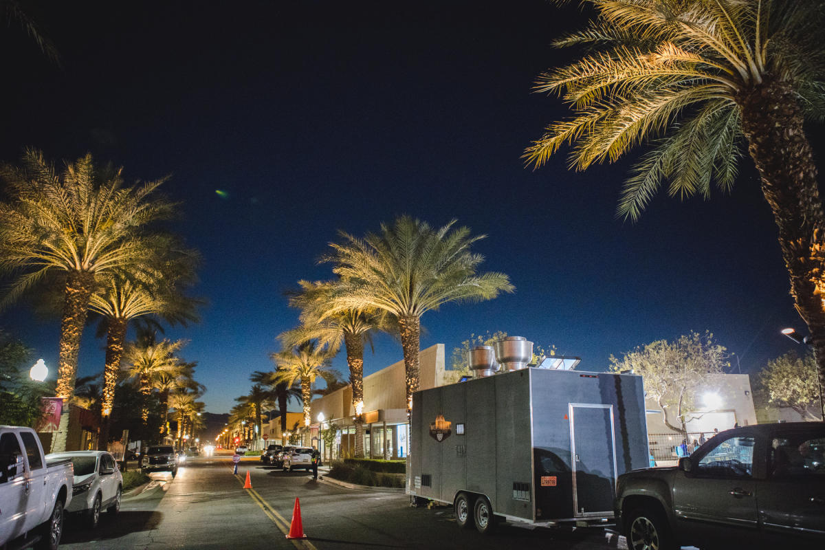 Food trucks lining the street at the Indio Food Park under the night sky.