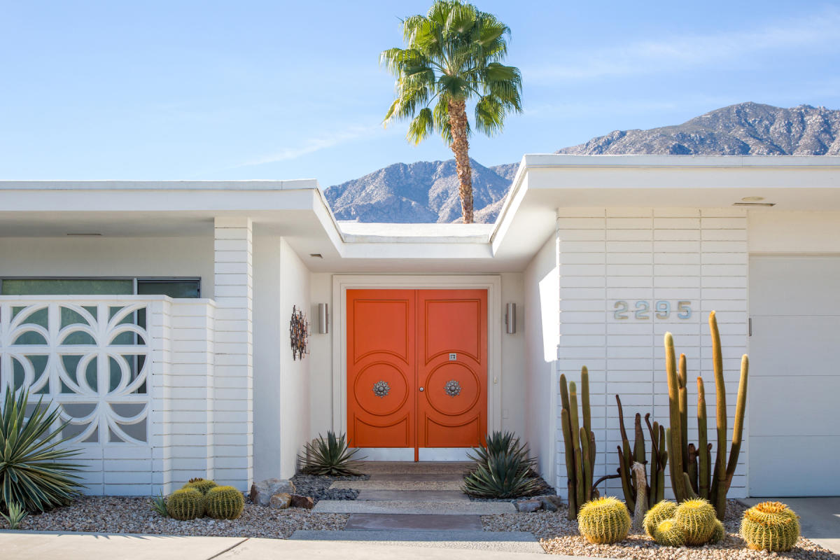 Modernism house with pretty palm tree background and orange door.