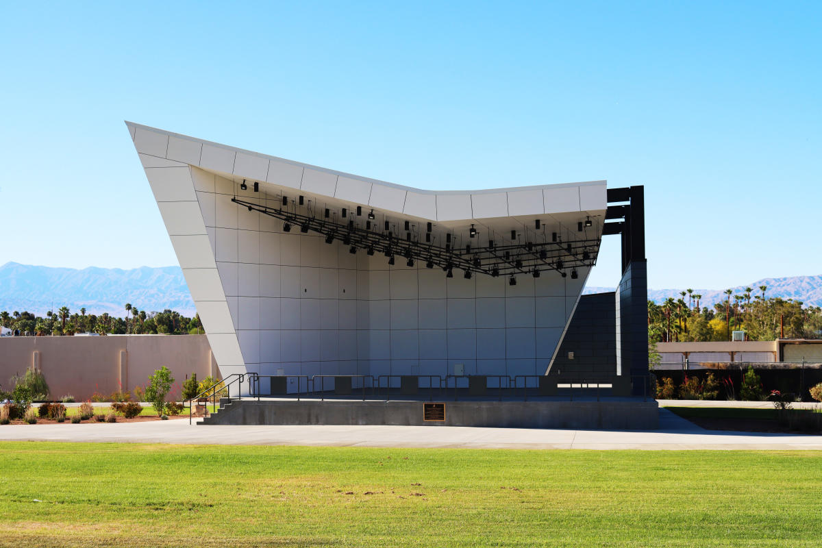 A sloped concrete stage, surrounded by a large green lawn.
