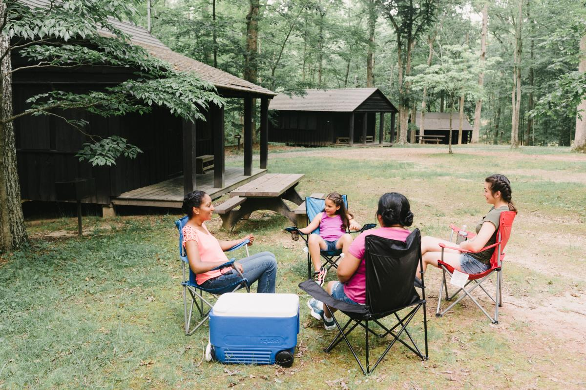 People sitting in folding chairs outside of a cabin