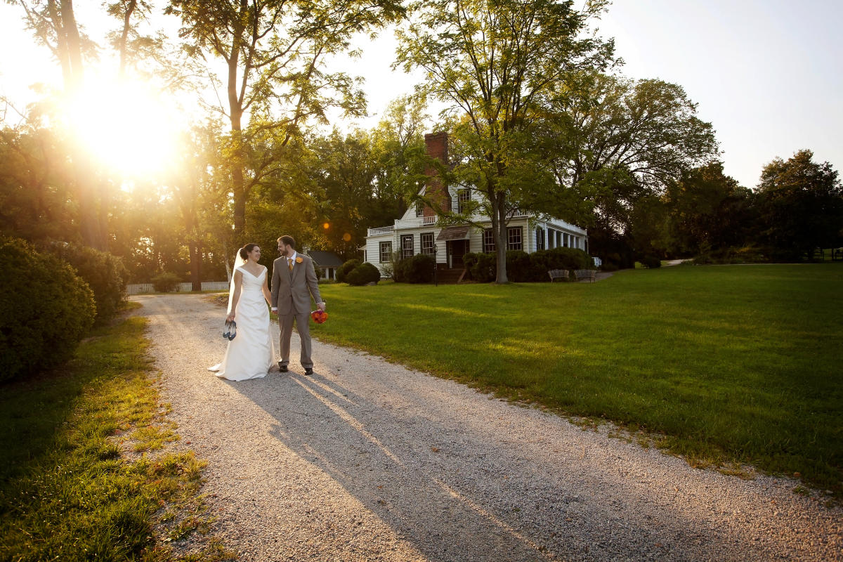Bride and Groom walking along path in front of Rippon Lodge Historic Site