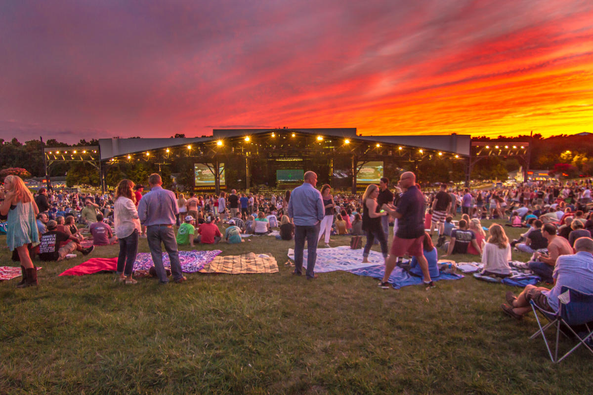 A crowd at an outdoor concert at Jiffy Lube Live at sunset