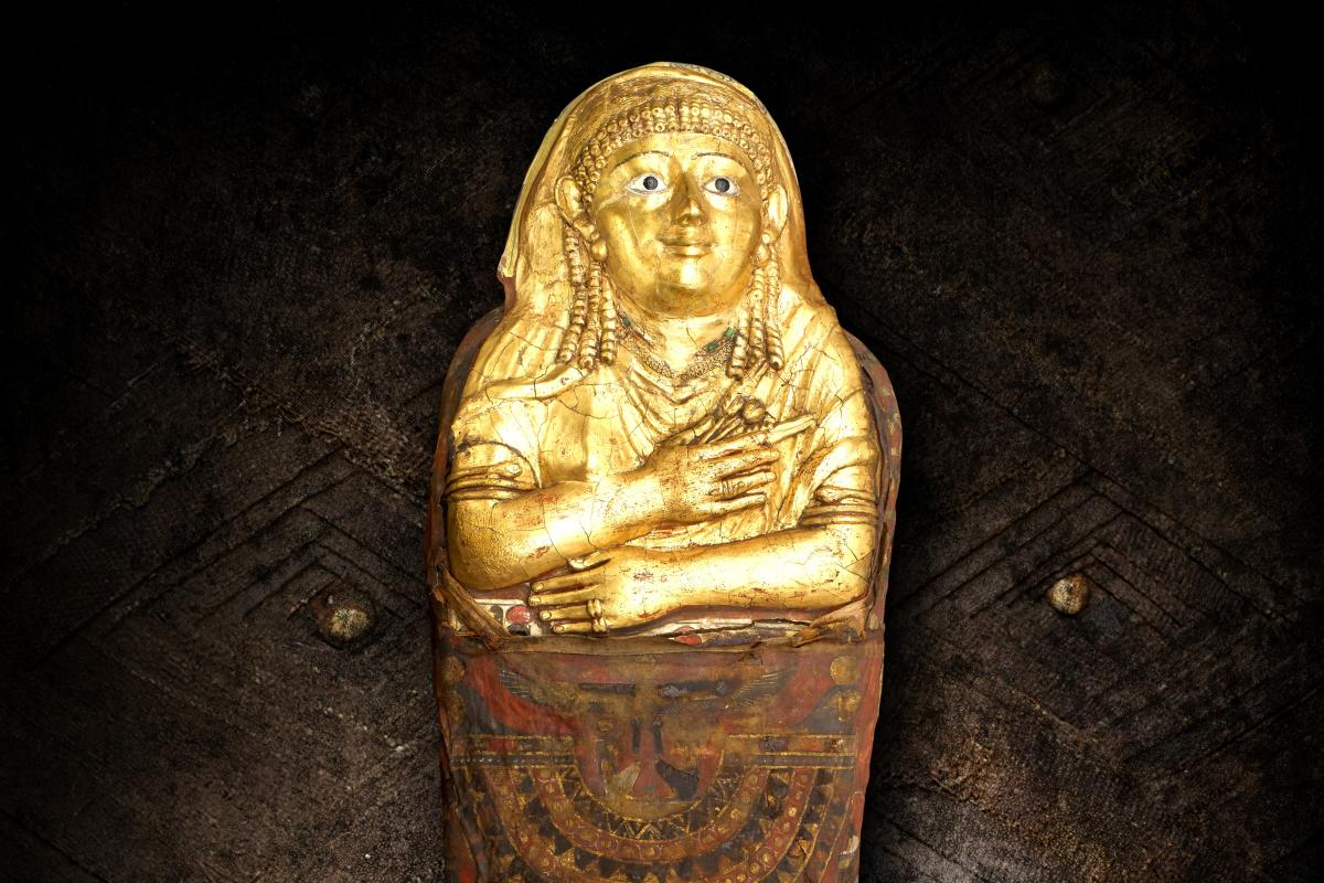Egyptian mummy, woman covered in gold wearing head covering and long earrings with arms crossed