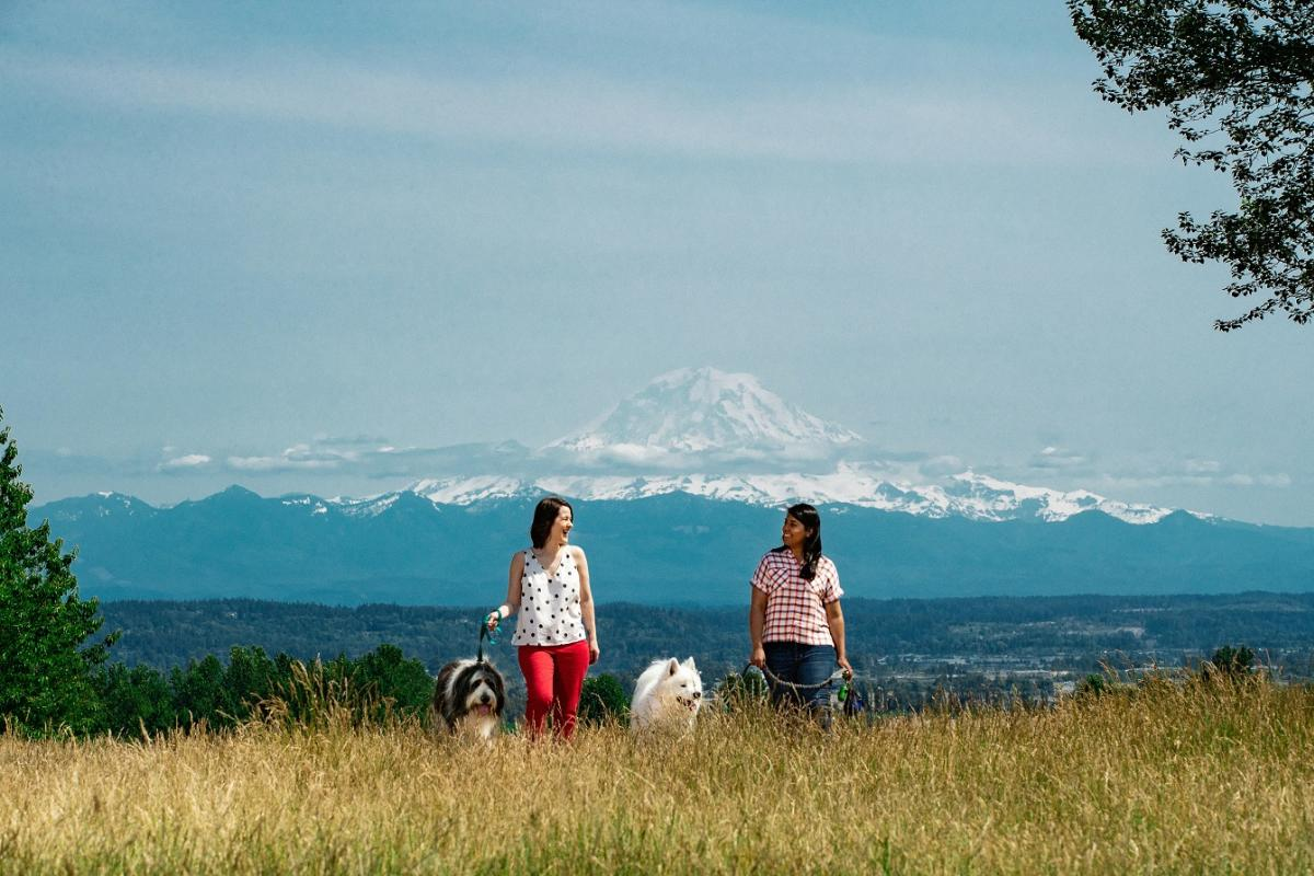 Women walking dogs in front of snow-capped Mount Rainier
