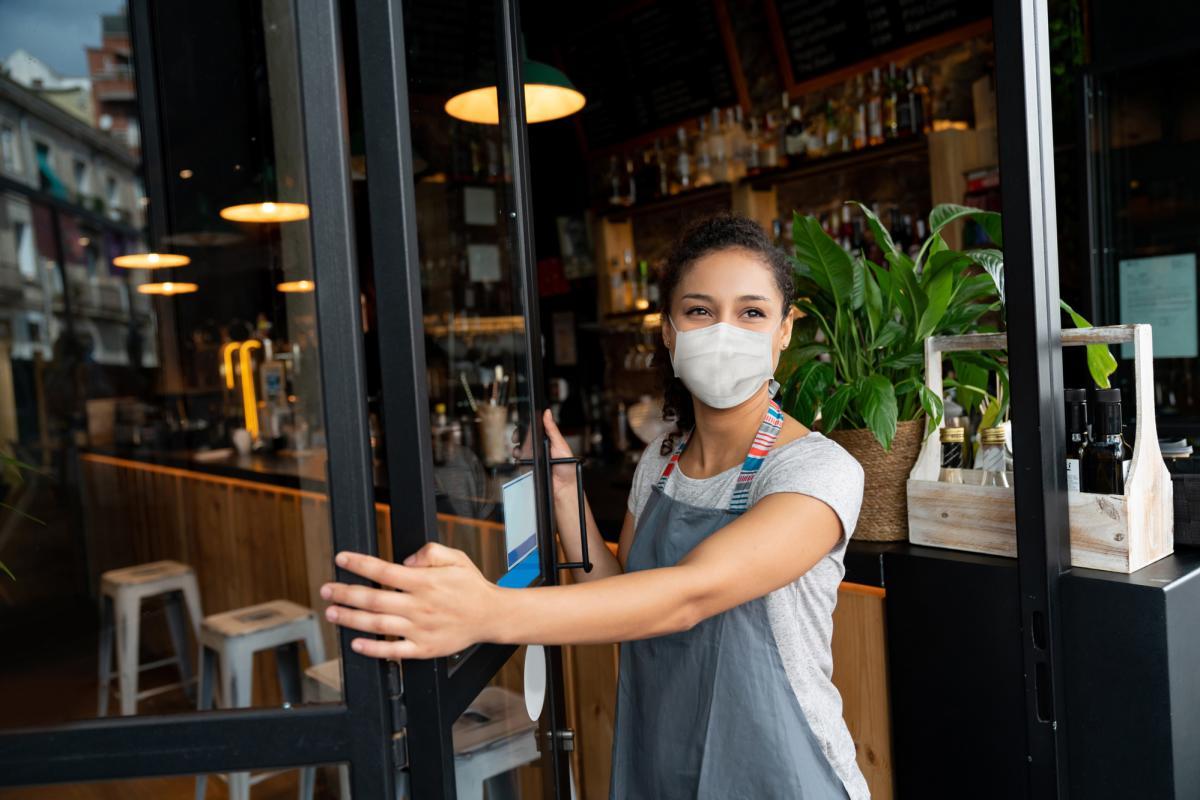 women wearing mask holding store door open