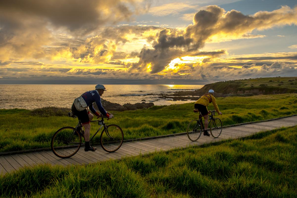 two men biking along the beach at sunset