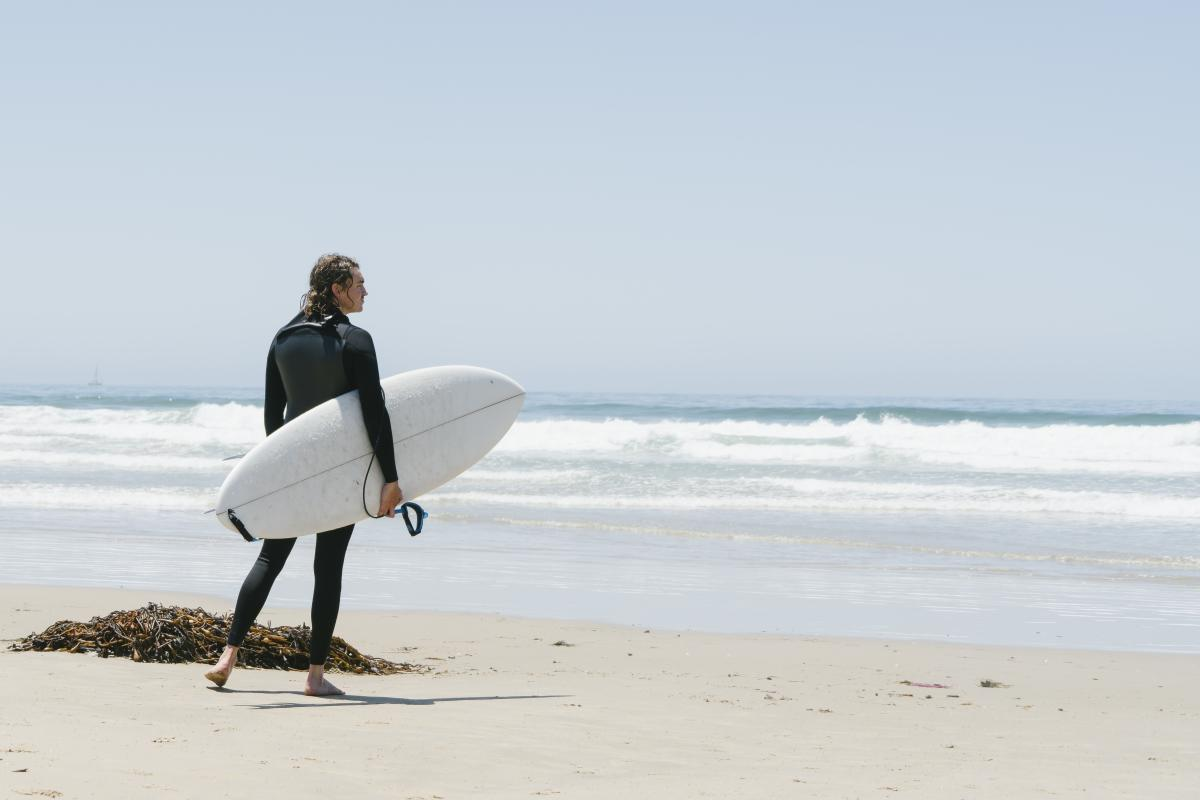 Surfer standing on the beach in SLO CAL