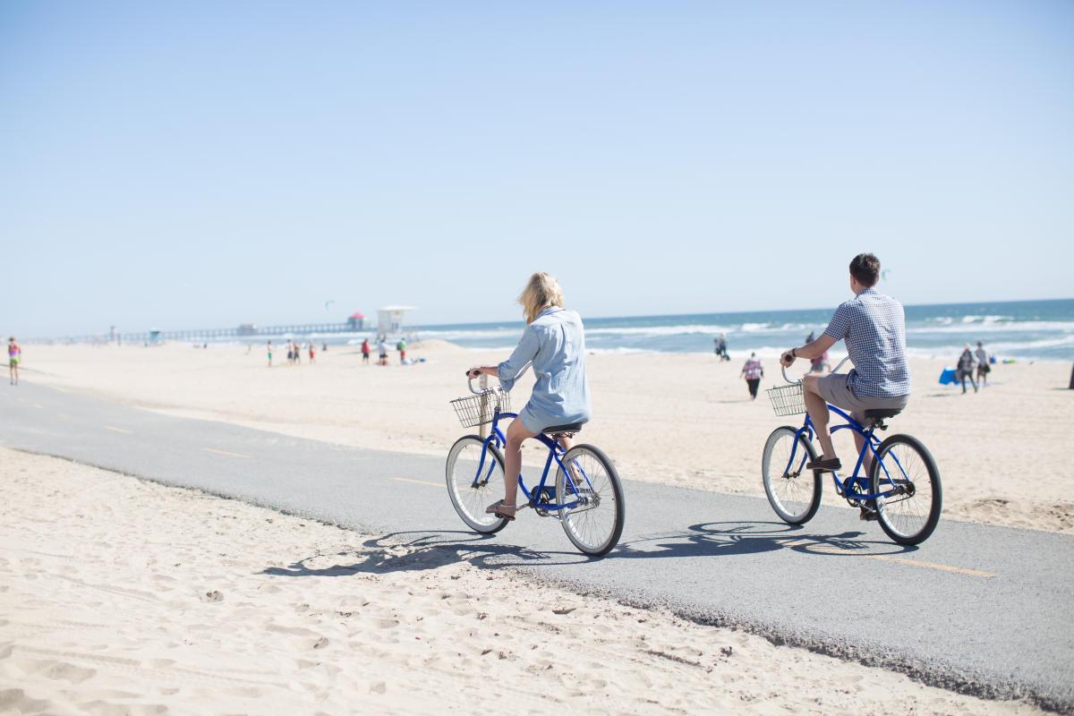 People Biking on the beach in Huntington Beach