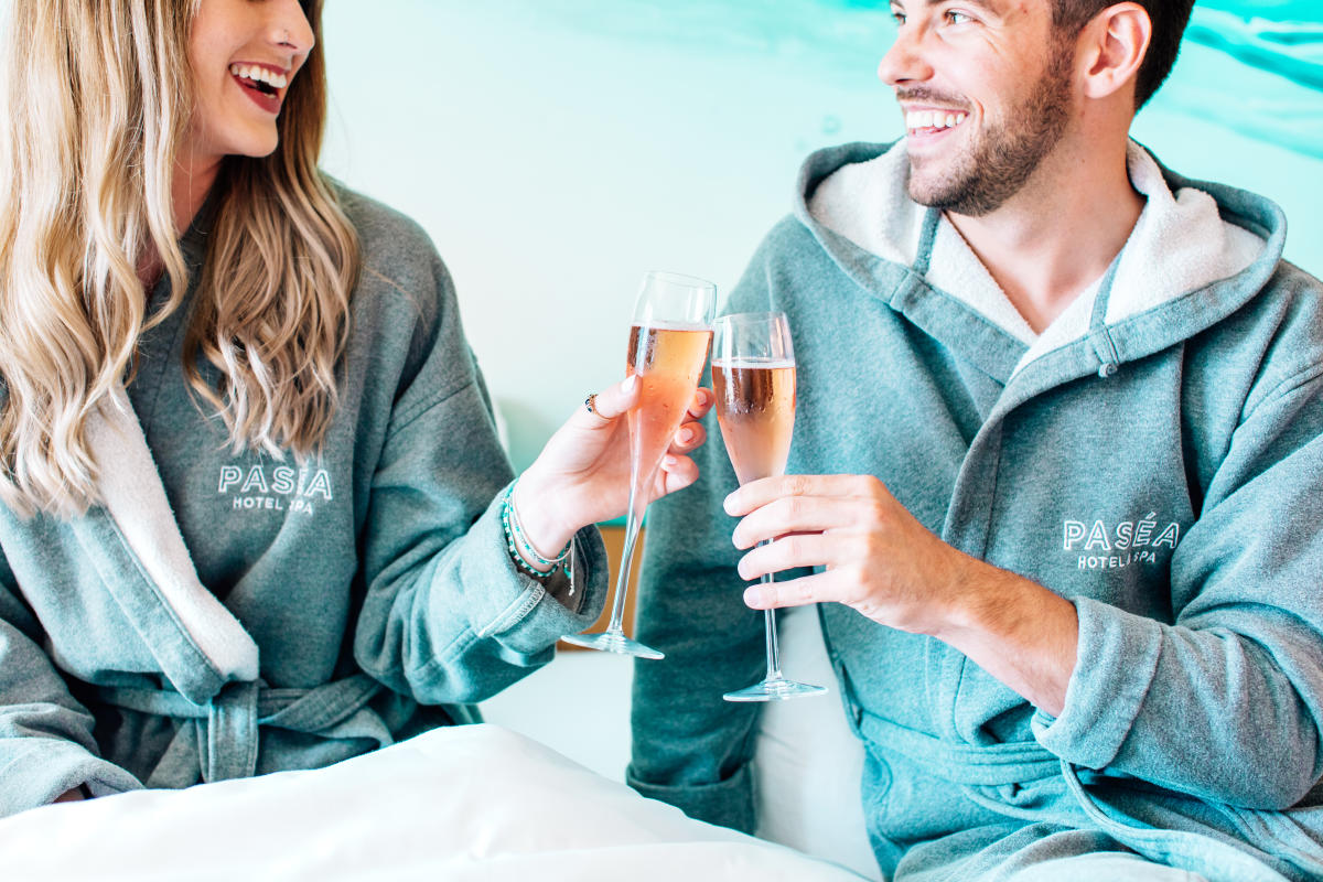 Smiling couple toasting champagne at the Pasea Hotel & Spa in Huntington Beach