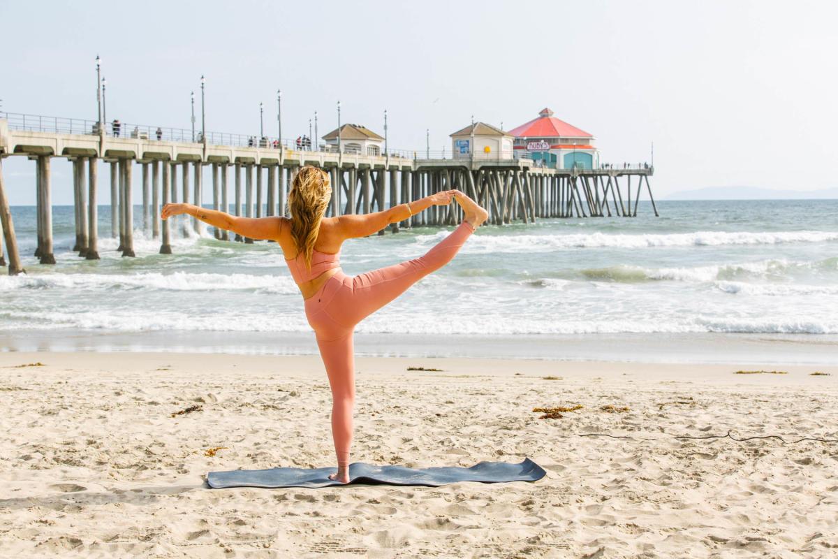 women doing a yoga pose by the Huntington Beach Pier