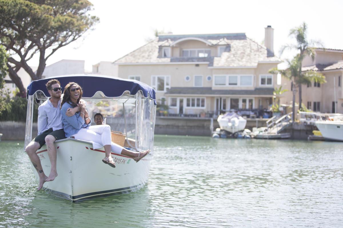Smiling couple enjoying a boat ride through Huntington Harbour in Huntington Beach