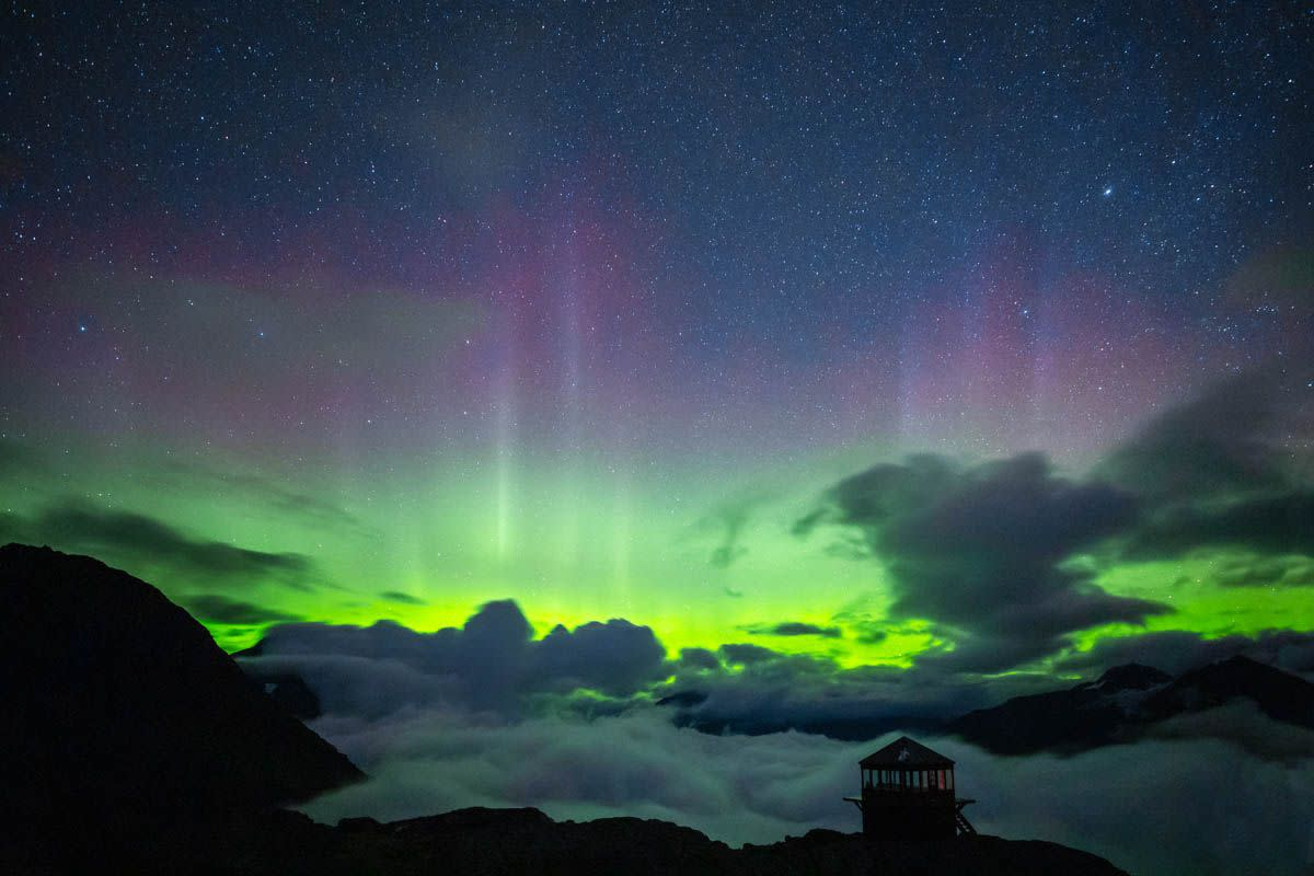 a small chalet in front of clouds, aurora, and night sky