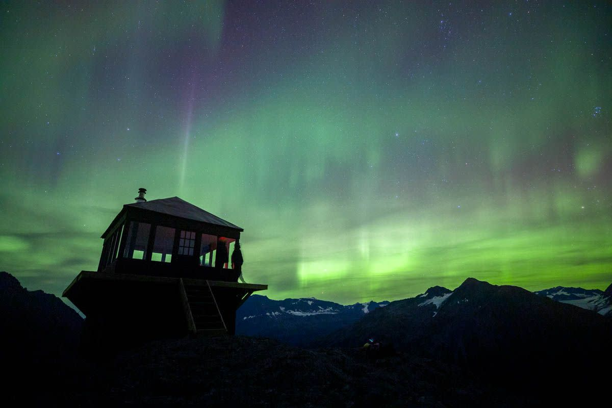 a chalet lodge in the mountains with aurora in the sky