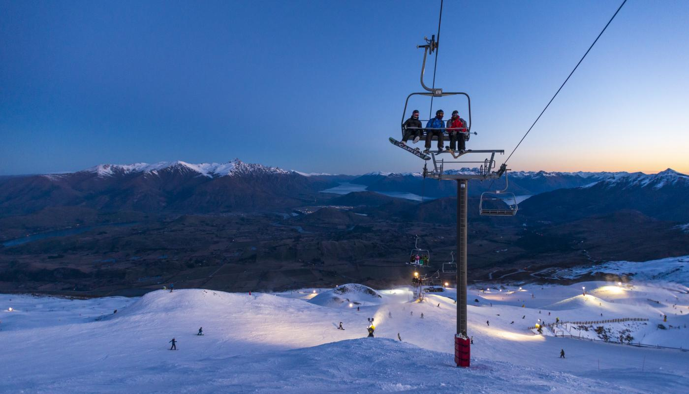 Friends on a chairlift at Coronet Peak Night Ski