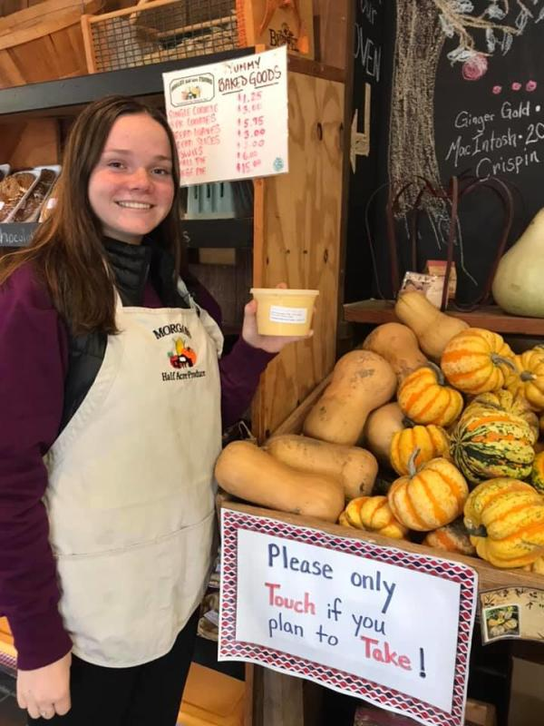 Employee showing off produce at Morgan's Half Acre Produce